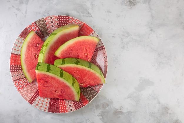 Grandes pedaços de melancia crua vermelha em um prato e fundo cinza