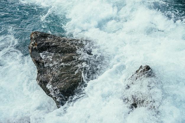 Grandes pedras em água azul de close-up de rio de montanha.