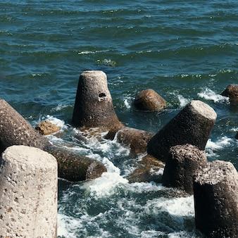 Grandes pedras estão na praia, em frente às ondas.