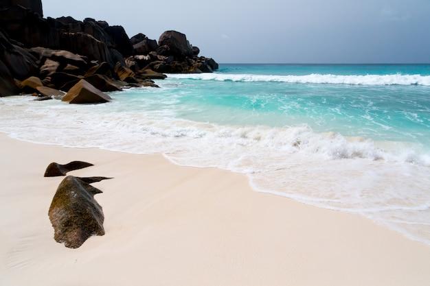 Grandes pedras na praia com areia branca