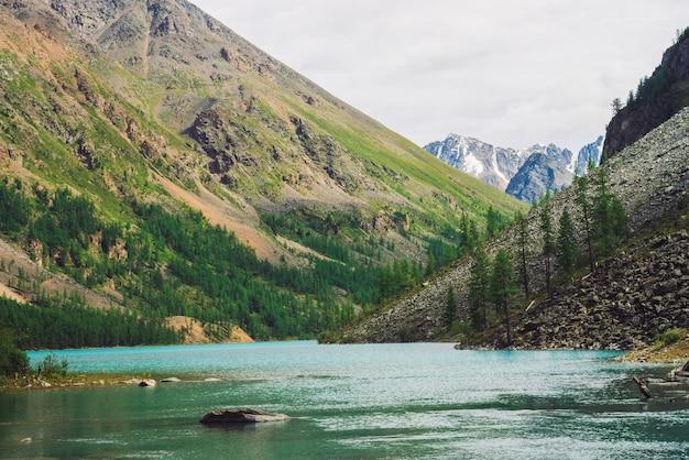 Grandes pedregulhos na água do lago de montanha na cena de montanhas gigantes com floresta de coníferas