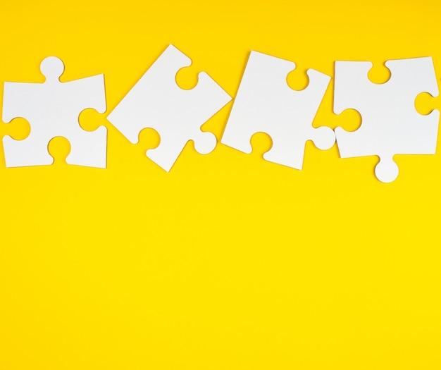 Grandes quebra-cabeças brancos em branco sobre fundo amarelo