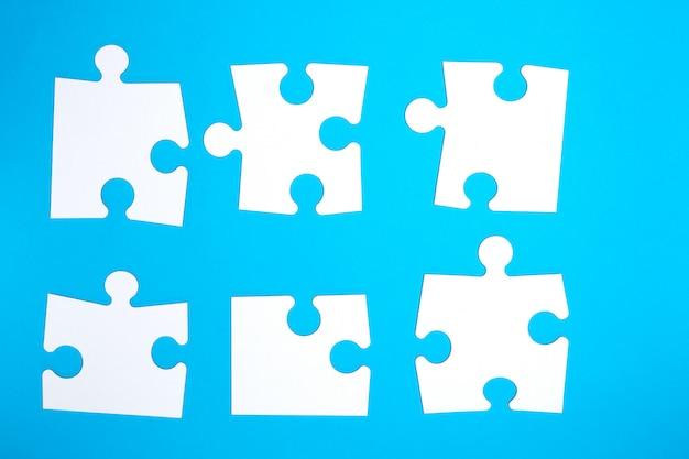 Grandes quebra-cabeças brancos vazios em azul
