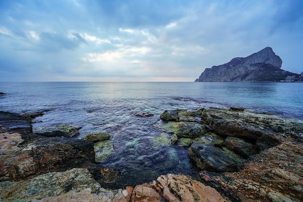 Grandes rochas na praia e as ondas batendo contra elas.
