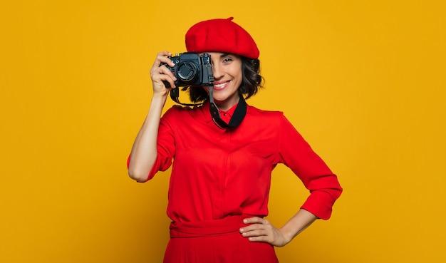 Grandes sorrisos agradáveis, pessoal! linda dentuça sorridente de férias, vestida de estilo francês, carregando uma câmera em uma alça no pescoço, pronta para fazer uma foto.