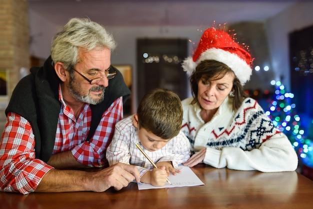 Grandparents com o neto de escrita de santa carta