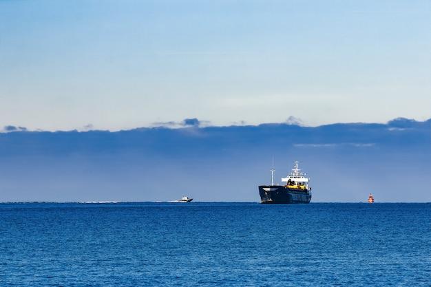 Graneleiro preto à vela. navio de carga com escavadeira de longo alcance se movendo em águas paradas em dia de sol à beira-mar