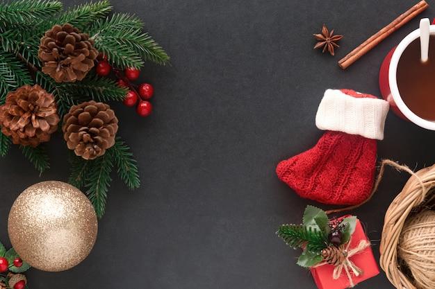 Granito preto com meia vermelha, folha de pinheiro e cones, bolas de azevinho, bugiganga e chocolate quente no natal
