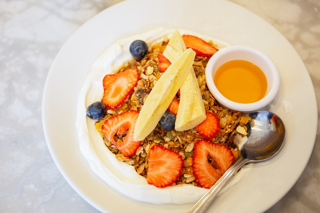 Granola caseira com iogurte e frutas mistas e mel de vista superior.