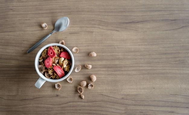 Granola caseira com leite no café da manhã na mesa de madeira. vista do topo