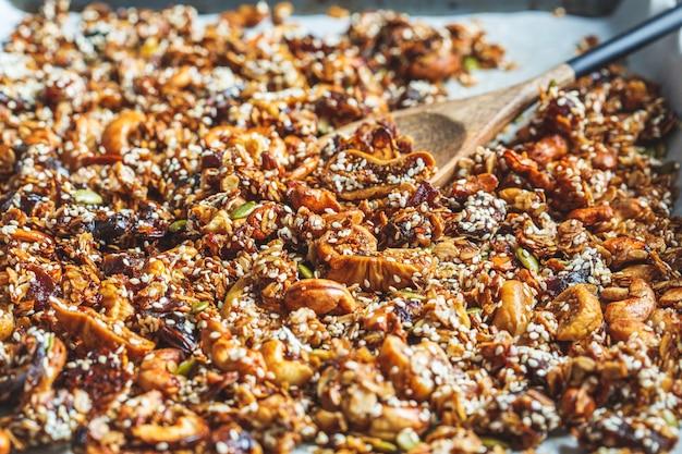 Granola caseira crocante com nozes, frutas secas e sementes de gergelim em uma assadeira.