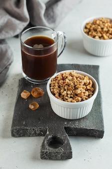 Granola caseira em uma tigela branca com caramelo e uma xícara de café