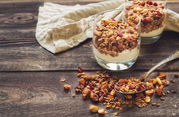 Granola caseira, muesli com nozes e cranberries secas e iogurte em copos na superfície de madeira rústica. café da manhã saudável.