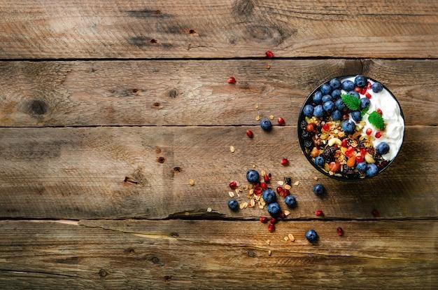 Granola caseira saborosa, iogurte, frutas orgânicas frescas, romã, hortelã