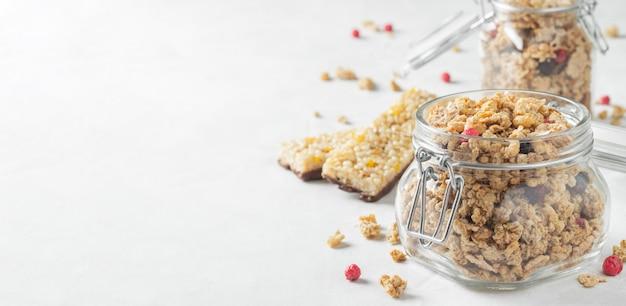 Granola caseiro com bagas em um frasco de pedreiro no fundo branco.