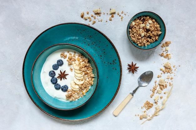 Granola caseiro de café da manhã, muesli com mirtilo fresco maduro, banana, chocolate branco e iogurte natural