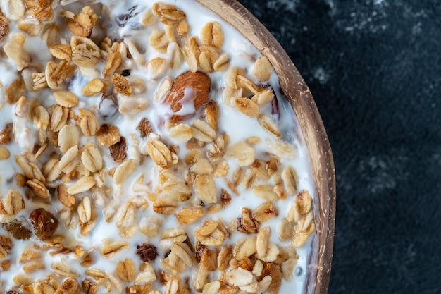 Granola com aveia, frutas secas, mel, passas, amora seca, amêndoa e castanha de caju com iogurte em uma tigela de coco, close up, vista de cima. conceito de café da manhã saudável