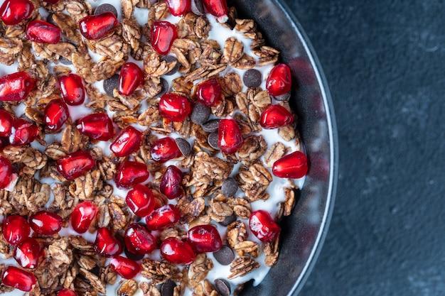 Granola com aveia, frutas secas, mel, passas, gotas de chocolate, nozes e sementes de romã vermelha com iogurte em uma tigela preta, close-up, vista superior. conceito de café da manhã saudável