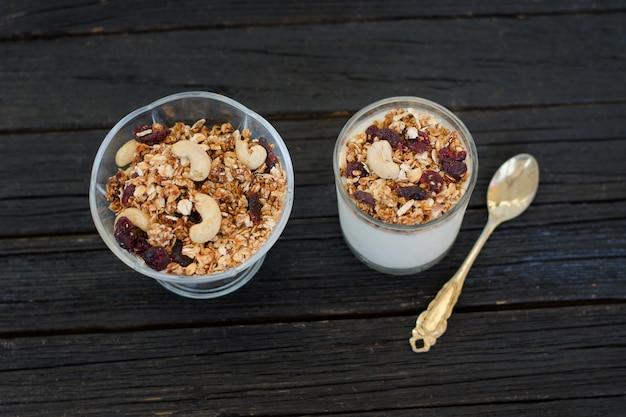 Granola com frutas e iogurte em uma mesa de madeira preta. pequeno-almoço americano tradicional