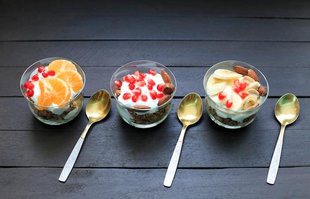 Granola com iogurte e frutas em copo pequeno.