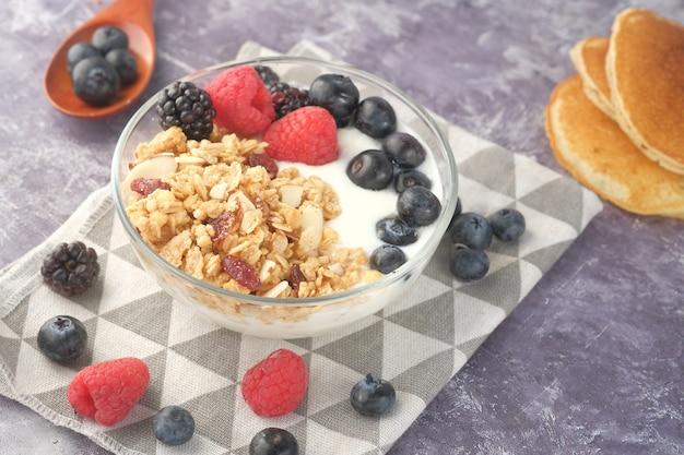Granola com iogurte e frutas vermelhas em uma tigela na mesa preta
