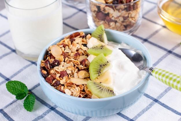 Granola com iogurte grego kiwi e banana em uma tigela com uma colher. dieta fitness para perda de peso, alimentação adequada e saborosa