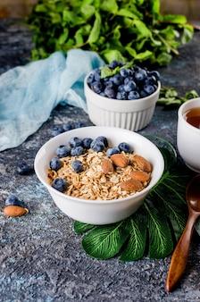 Granola com mirtilos em chapa branca e xícara de chá no café da manhã, muesli assado caseiro com nozes e mel para pouca doçura.