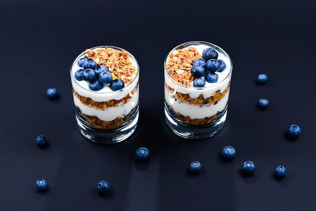 Granola cozido caseiro com iogurte e mirtilos em um copo em um fundo preto. espaço para texto ou design.