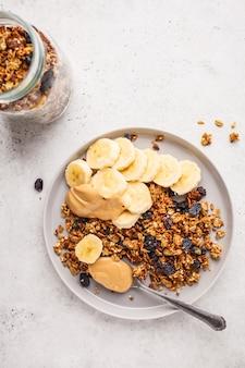 Granola cozido com manteiga das passas, da banana e de amendoim, vista superior, espaço da cópia.