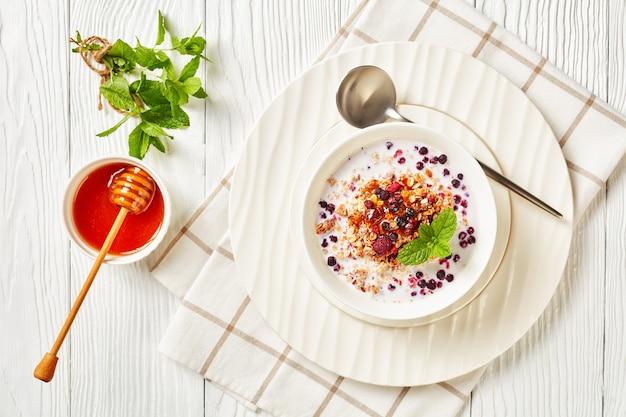 Granola de aveia com framboesas secas, mirtilos e nozes com leite e coberta com mel em uma tigela branca sobre uma mesa de madeira, vista de cima da paisagem, close-up, camada plana