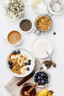 Granola de aveia com iogurte, mel, bananas frescas, mirtilos, sementes de chia na tigela e xícara de café