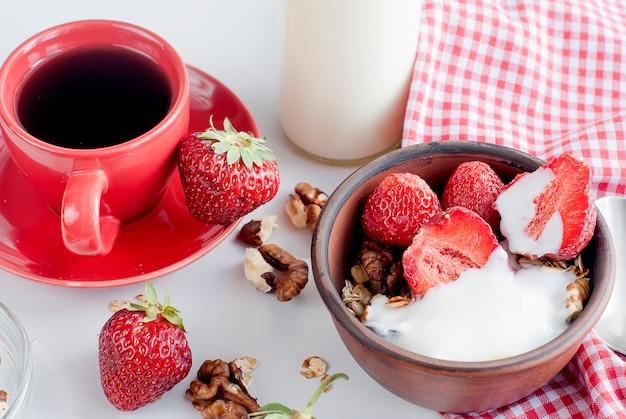Granola de café da manhã, morango e uma xícara de café