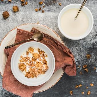 Granola de vista superior com leite orgânico em cima da mesa