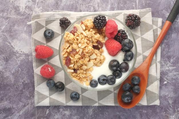 Granola e frutas vermelhas em uma tigela rosa