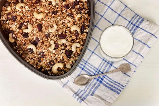 Granola em uma assadeira e iogurte em um fundo branco claro.