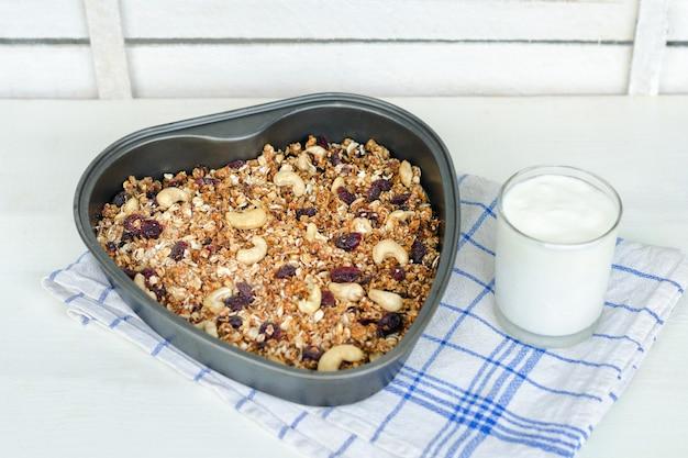 Granola em uma assadeira e iogurte em uma superfície branca clara