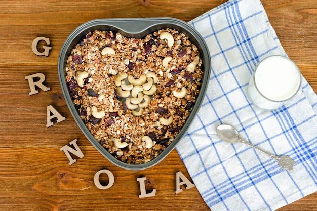 Granola em uma assadeira em forma de coração. iogurte, toalha, inscrição letras de madeira granola. comida