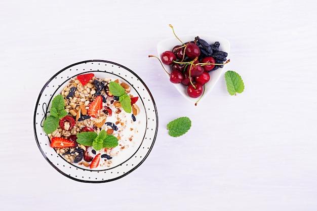 Granola, morangos, cereja, madressilva, nozes e iogurte em uma tigela