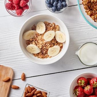 Granola paleo sem aveia, sem grãos, misturada com fatia de banana, em uma tigela com nozes, framboesas, morangos, mirtilos e leite em uma garrafa em um fundo branco de madeira