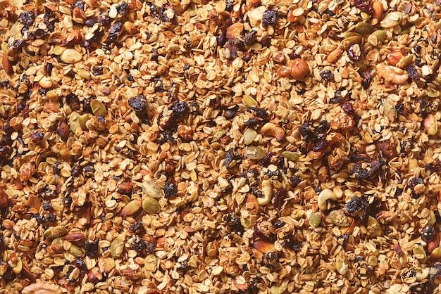 Granola roasted caseiro orgânica com porcas e passas na folha de cozimento. comida para o café da manhã. fundo de refeição, textura de granola
