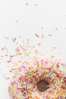Granulado colorido sobre o donut em pano de fundo branco