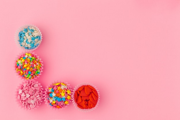 Granulado de açúcar, decoração para bolo e sorvete e biscoitos no fundo rosa