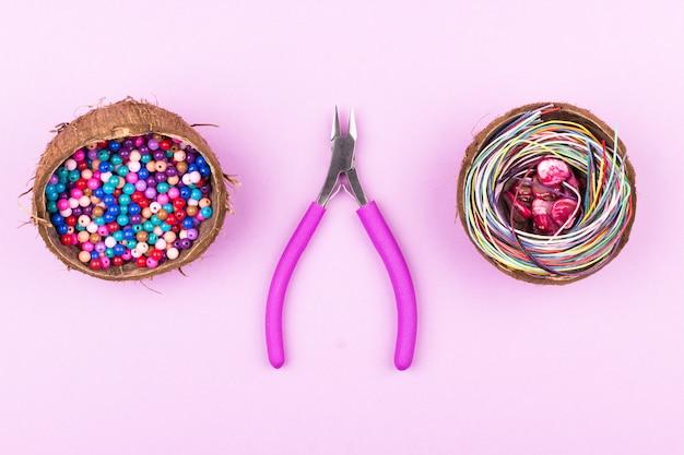 Grânulos coloridos em metades de coco, cordas, contas de concha e alicates em fundo rosa