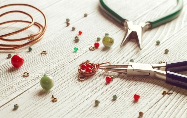 Grânulos coloridos, fios de cobre e ferramentas de joias em uma mesa de luz