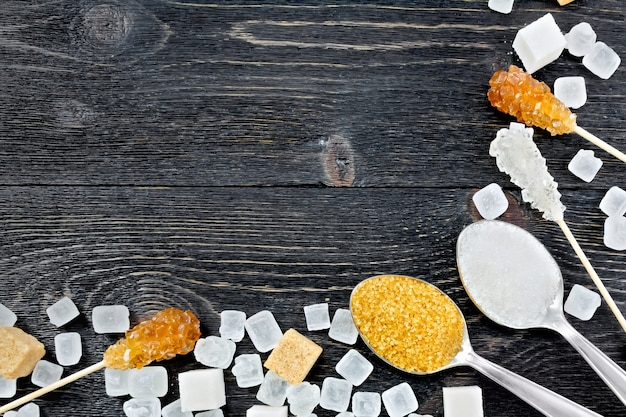 Grânulos de açúcar mascavo e branco em colheres, cubos e cristais em uma vara na forma de uma moldura no fundo de uma placa de madeira preta