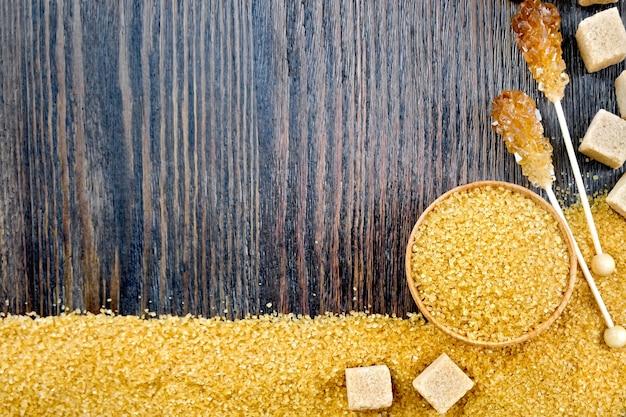 Grânulos de açúcar mascavo em uma tigela, cubos e cristais em uma vara na forma de uma moldura no fundo de uma placa de madeira