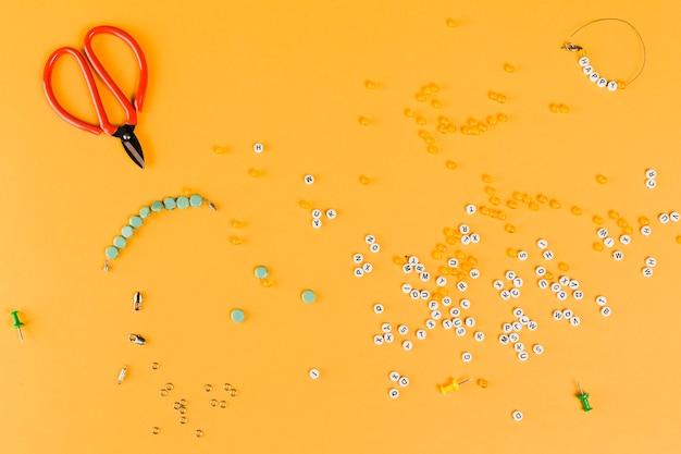 Grânulos de carta e gancho com tesoura em fundo amarelo
