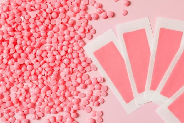 Grânulos de cera quente de depilação rosa e tiras depilatórias de cera para áreas delicadas em um fundo rosa