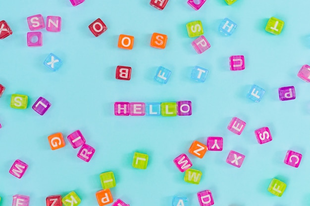 Grânulos de cubo plástico multicoloridos com letras e palavra olá. textura de fundo do alfabeto inglês