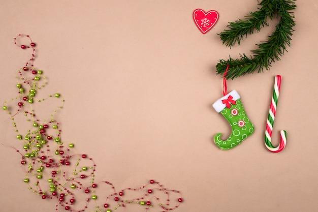 Grânulos de natal festivos, uma bota vermelho-verde para doces pendurados em um fundo de galho de árvore de natal